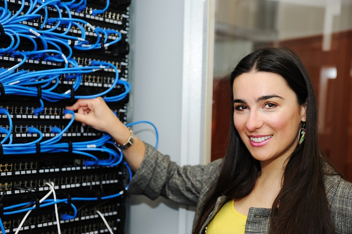Female administrator at server room connecting wires