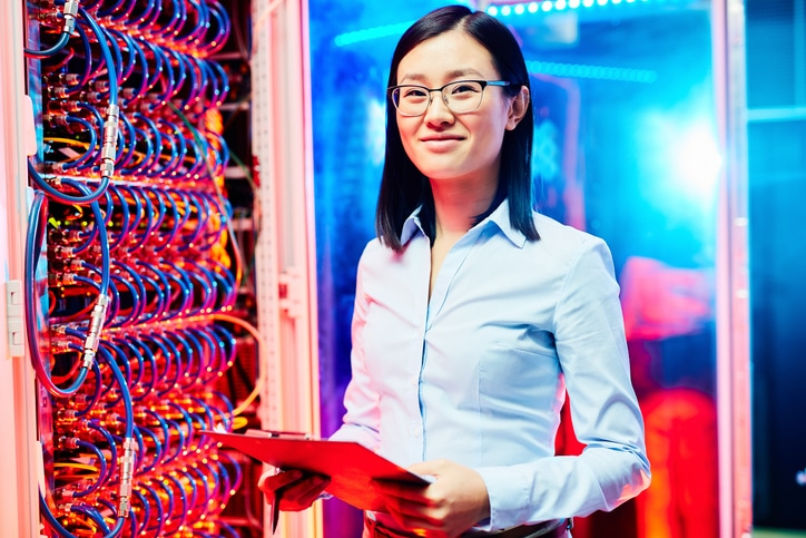 Young researcher looking at camera in data center